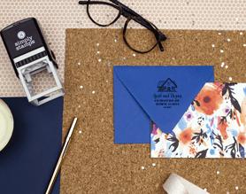 custom return address stamp on desk with envelope